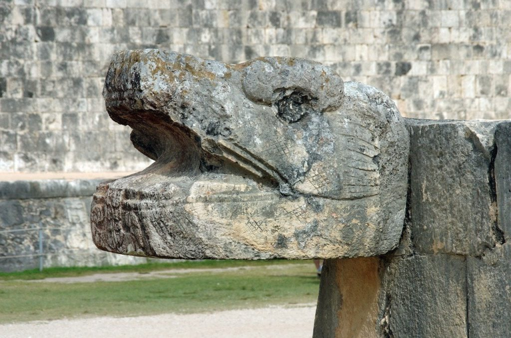 A huge serpent's head carved in stone at the bottom of the stairway in Chichen Itza