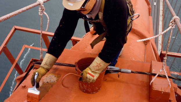 A painter touches up one of the bridge's cables.