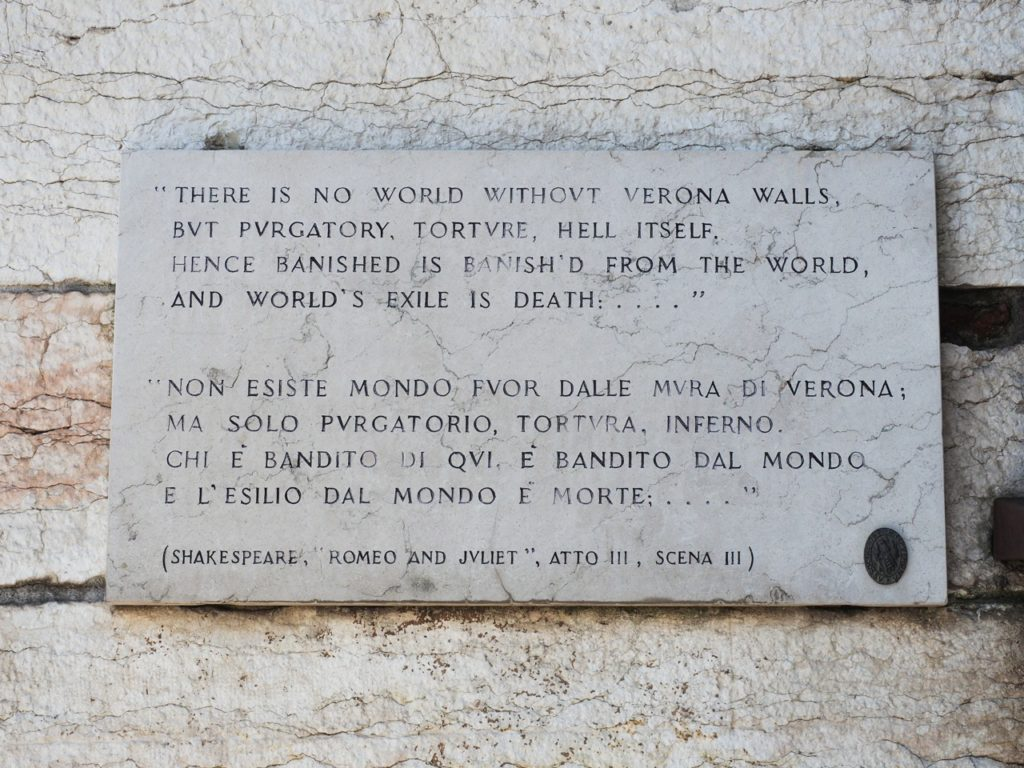 A marble plaque is placed on Verona's ancient walls in Piazza Bra, with a quote from Romeo's exile.